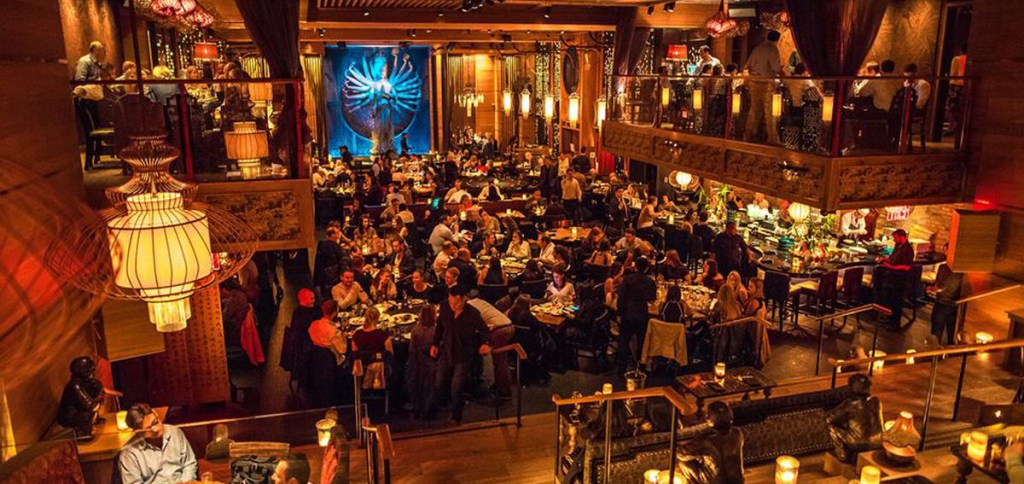 Full view of a Tao Group property, lots of diners with dim lighting and Asian-inspired decor.